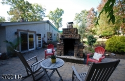 Large Stone Woodburning Fireplace sits on Tiled Patio, perfect for cold nights!