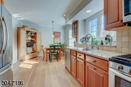Sunny and bright renovated Eat in kitchen with Quartz countertops and stainless appliances.