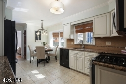 Renovated eat-in kitchen with glazed shaker style cabinets, granite counters, stone subway tile back splash, bamboo shades