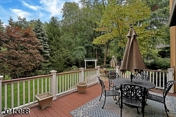 The deck overlooks private rear grounds with a natural privacy border of deciduous and evergreen foliage.