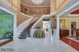 """16 x 14 Two story Foyer featuring custom solid wood Double door entry, Schonbek Crystal Chandelier, Sentry Closets, Curved Stair case and custom Handrail & Iron Balusters, wool carpert runner, 24"""" Travertine Tile flooring"""
