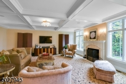 """22'8"""" x 18'4"""" Coffered Ceiling, American Brass & Crystal Chandelier and sconces, wood burning fireplace with travertine surround and custom wood mantel, Kane wool carpeting"""