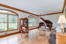 Grand room with custom moldings,hard wood floor and floor to ceiling windows