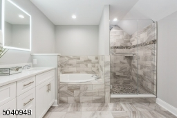 A light reflected custom mirrors keeps thing clear and serene.All showerheads overhead and hand held sprays can be turned on at the same time for an amazing spa like experience. Pebbled floor shower.