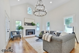 Stunning family room with vaulted ceilings, feature chandelier, fireplace and sliders to a blue stone patio overlooking a meticulously landscaped backyard and 2-car detached garage