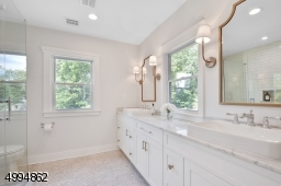 Spa-like master bath has walk-in shower with custom shower glass, 10ft double vanities, marble tile and countertops, plenty of natural sunlight and linen closet