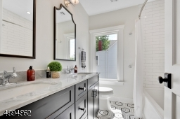 Stylish full bath with double vanities, marble countertop and linen closet