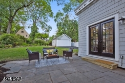 Blue stone patio overlooking a meticulously landscaped backyard and 2-car detached garage