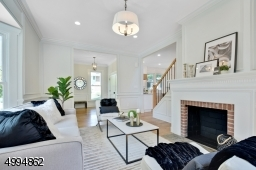 Formal living room with floor to ceiling wainscoting, original fireplace and bay window