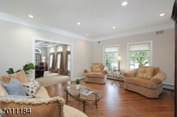 Bright and sunny living room that has newly refinished wood floors, recessed lighting and large windows.
