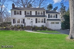 Beautifully landscaped front yard! White wood-shingled siding complimented by classic black shutters.