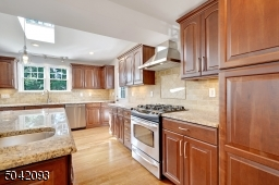 Granite counters, tile backsplash, stainless steel appliances, under cabinet lighting.