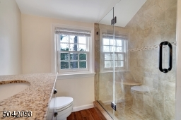 Tiled walk-in shower with floor to ceiling glass door entry and separate Linen Closet.