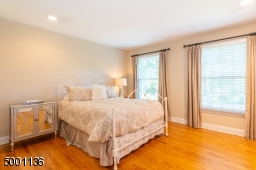 Large bedroom with recessed lighting located near double sink vanity hall bathroom with additional closet space