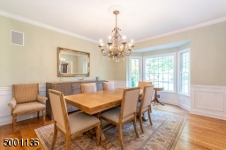 Formal Dining Room with wainscoting picture frame molding, built in speakers and a bay window make dinner parties great fun!