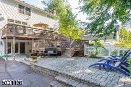 View of double tiered deck, lower level walk out, paverstone patio and fenced in grassy level yard