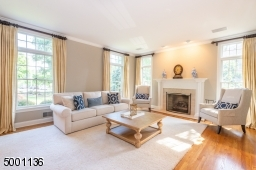 Bright and Airy formal living room with transom windows, beautiful oak wood floors, a gas fireplace and french doors to create privacy from the family room