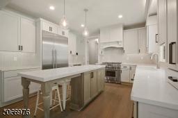Chef's EIK featuring, Smart, Thermador SS appliances including a six-burner stove, built-in microwave, dishwasher, quartz countertops, Medallion custom wood cabinetry, hardwood floors, chevron grey tile backsplash