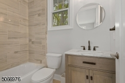 Bathroom with marble look tile floors, wood vanity with marble top, shower over tub with recessed light and three light sconce