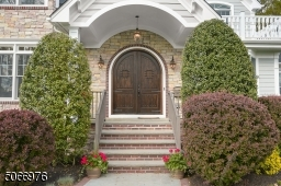 Bluestone walkway with brick border leads to Double solid wood, Speakeasy, Front Doors featuring curved wood surrounded by brick and stone, covered entryway with hanging lantern