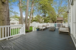 A large Hardi-Plank Deck overlooks the fenced-in level yard with play area / jungle gym, mature flower beds, trees and shed.