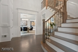 Double height Foyer featuring greige herringbone hardwood floors, crown moldings, paneled wall moldings, 2 coat closets, open staircase with decorative metal balusters and chandelier