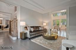 Living Room featuring hardwood floors, crown moldings, Bay windows, paneled walls