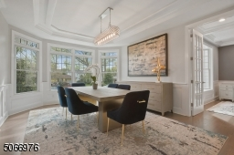 Dining Room featuring hardwood floors, paneled walls, recessed ceiling, 4 Bay double windows with transom windows and modern light fixture