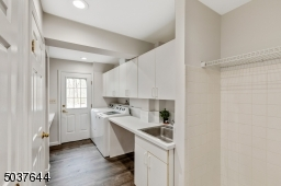 Mud RM / Laundry RM is located directly off of the kitchen & features direct access to attached garage, new wood-like plank flooring, closets w/built-ins, doggie shower, cabinetry, folding table, access to deck& driveway & laundry chute from Primary BDRM