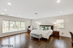 Primary Bedroom Wing with double privacy doors features hardwood floors, recessed lights, 4 fitted closets including 2 walk-ins, bay window, wood burning fireplace and built-in media area with flush cabinetry