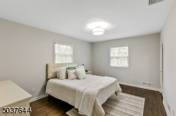 Bedroom 3 features hardwood floors, flushmount light, 2 windows and a fitted walk-in closet