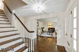 Foyer with solid wood Front Door with recessed panels and beveled sidelights, deep baseboard moldings, hardwood floors, modern flush mount light fixture, coat closet and open staircase