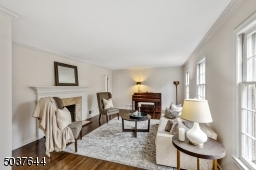 Living Room features deep baseboard moldings, crown moldings, hardwood floors, 3 oversized windows, statement gas fireplace with white mantle and marble surround