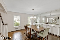 Dining Room with deep baseboard moldings, crown moldings, hardwood floors, wall-to-wall built-in buffet with concealed storage and custom mirror, modern chandelier and 2 oversized windows