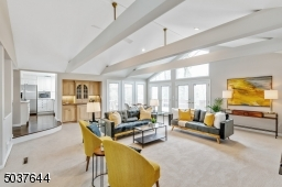 Great Room is completely open concept to EIK and features wall-to-wall carpeting, vaulted ceiling with beams, built-in Wet Bar with sink, refrigerator and glass doors, two sets of double French doors which access deck and a wall of triple Pella windows