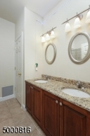 Two sinks, shower over bathtub and separate linen closet