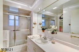 Attractive in neutral, white decor - double-sized vanity with newer sink, counter top, and commode. The tiled, shower-over-tub has glass doors. Recessed lighting.