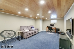 The basement rec room has a custom wood ceiling with recessed lights and cozy carpeting.
