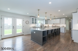 """Kitchen is huge a real WOW with doors to patio. Island has seating for 4 stools/chairs on island. Note the """"carrera marble"""" quartz counters"""