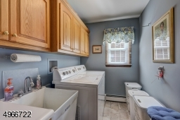 """Located on the first floor. Laudry room is 5'.9"""" x 8'.9"""" with oak cabinets and utility sink."""