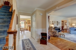 """Entrance Foyer is 9"""" x 7' with tiled flooring and wainscoting crown molding."""