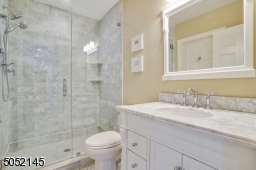 Full Bath featuring black and white basket weave marble floor, white vanity with grey and white marble top and frameless glass enclosed shower with grey marble subway tile