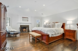 Primary Bedroom Suite featuring tray ceiling with recessed lights, hardwood floors, deep baseboard moldings, gas starter wood burning fireplace with white moldings flanked by two oversized windows