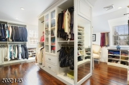 Primary Dressing Room / Walk-In Closet featuring built-in ?furniture? and windows