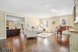 Living Room is open to Foyer & features hardwood floors, deep baseboard moldings, wood burning fireplace, built-in open shelving w/ lower cabinetry&2 sets of French doors which lead to glass enclosed Sunroom / Office and Family Room