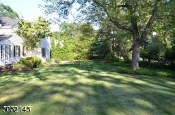 Lushly landscaped property with mature plantings and flower beds