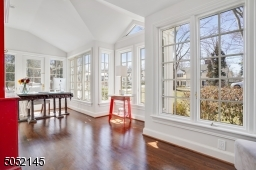 Sunroom / office featuring hardwood floors, vaulted ceiling, two exposures of floor-to-ceiling windows, and French door to private brick patio