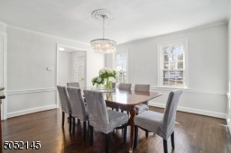Dining Room is open to Foyer and features hardwood floors, chair rail, built-in corner china cabinet and 2 exposures of windows