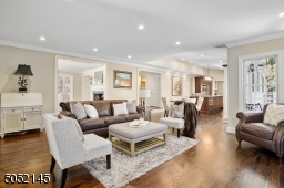 Family Room is step down from Living RM & Foyer, open concept to EIK & features hardwood floors, baseboard moldings, recessed lights, fireplace w/ built-in flatscreen TV flanked by oversized windows, French sliders to deck / patio