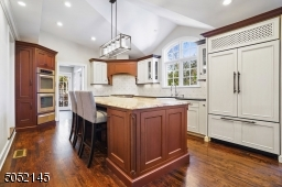 Gourmet Chef?s Eat-In Kitchen featuring WoodMode custom cabinetry, granite countertops, hardwood floors, crown moldings, recessed lights, modern light fixture over island, large island with seating and abundant storage, high-end appliances.